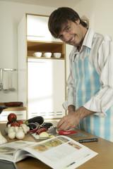 Junger Mann schneidet Gemüse in der Küche, Portrait, Nahaufnahme