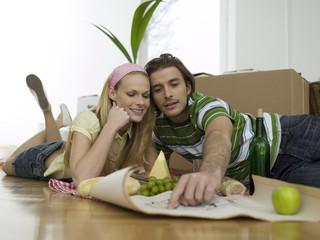 Paar diskutiert einen Grundriss, Bauplan