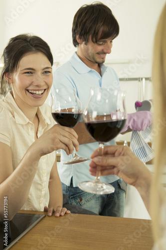Frauen st0ßen an, Mann arbeitet im Hintergrund, lächelnd
