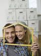 Junges Paar formt ein Haus aus einem Zollstock