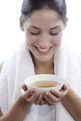Junge Frau hält Teeschale, lächelnd, Nahaufnahme
