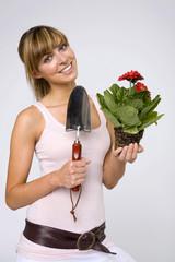 Junge Frau mit Topfpflanze und Kelle, lächelnd