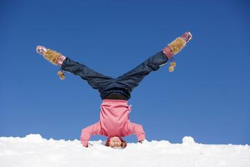 Österreich, Mädchen macht Kopfstand im Schnee
