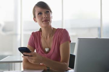 Geschäftsfrau mit einem Palmtop, sitzt am Schreibtisch