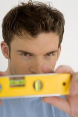Junger mann mit gelber Wasserwaage, Portrait