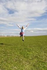 Mädchen springt im Feld, Arme hoch