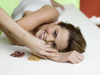 Junge Frau liegt auf dem Bett mit Gewürz, Lächeln, Portrait