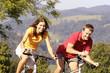 Junges Paar fährt Fahrrad, lächelnd, Berge im Hintergrund