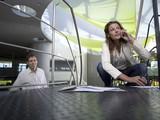Junge Unternehmerin mit Mobiltelefon, Papiere fallen auf dem Boden