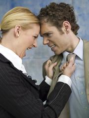 Geschäftsfrau streitet mit Kollegen, zieht an Krawatte