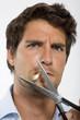 Junger Mann schneidet Zigarette mit Schere, Nahaufnahme, Portrait