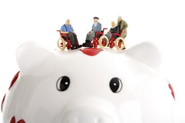 Figuren auf Rollstühlen mit Sparschwein