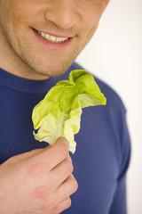 Junger Mann mit Salatblatt, lächelnd, Nahaufnahme
