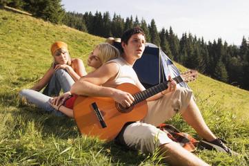 Junge Leute auf Wiese, Mann spielt Gitarre