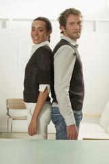 Junges Paar Rücken an Rücken stehend, Seitenansicht, Portrait