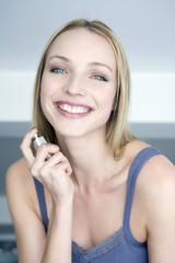 Junge Frau benutzt Parfüm