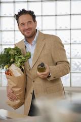 Mann steht in der Küche, hält Papiertüte und Weinflasche, lächelnd