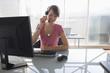 Frau arbeitet am Computer, mit Headset