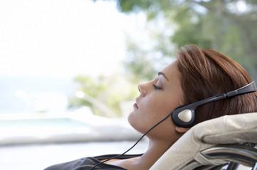 Frau mit Kopfhörern, die Augen geschlossen