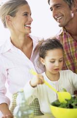 Eltern mit Tochter machen Salat