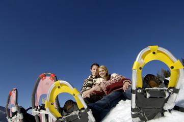 Junges Paar sitzt im Schnee mit Schneeschuhen