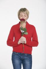 Junge Frau riecht an einer Rose, Porträt