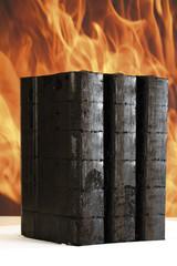 Gestapelte Briketts, Feuer im Hintergrund