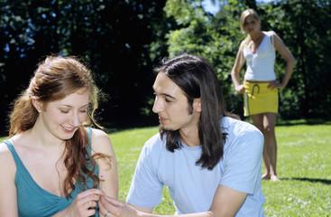 Junger Mann, der Blume bis zur jungen Frau, Nahaufnahme