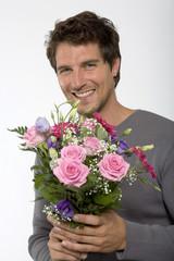 Junger Mann mit Blumenstrauß, lächelnd, Nahaufnahme, Portrait