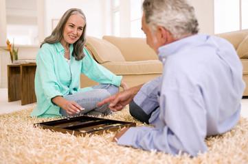Älteres Paar spielt Backgammon in Wohnzimmer, lächelnd