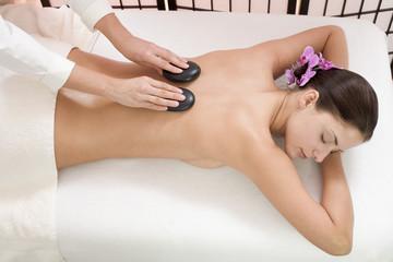Junge Frau bei Massage mit heißen Steinen