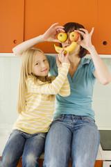 Mutter und Tochter in der Küche, Mutter mit Äpfel vor den Augen,