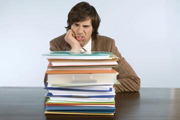 Mann sitzt auf dem Schreibtisch mit Stapel von Ordnern