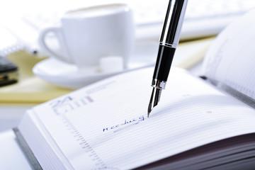 Tagebuch und Stift, Tasse Kaffee im Hintergrund