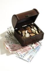 Kleine Truhe voller Münzen, stehend auf Banknoten, erhöhte Ansicht