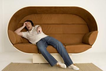 Junger Mann liegt auf dem Sofa, Kopfhörer und mit Fernbedienung
