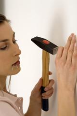 Junge Frau schlägt Nagel in die Wand mit Hammer, Nahaufnahme