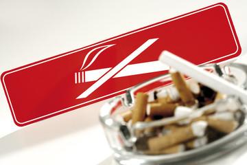 Voller Aschenbecher vor Rauchverbot Schild