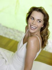 Frau sitzt auf dem Bett, lächelt