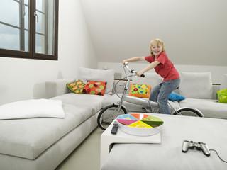 Junge fährt Fahrrad im Wohnzimmer