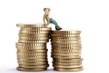 Figur stützte sich auf Stapel von Münzen, mit Hut