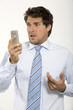 Junger Geschäftsmann schaut auf sein Handy, Nahaufnahme