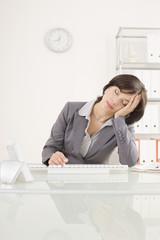 Geschäftsfrau müde bei der Arbeit, Hand am Kopf