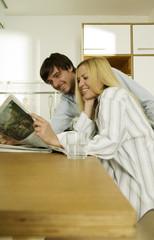 Junges Paar liest Zeitung in Küche, Lächeln
