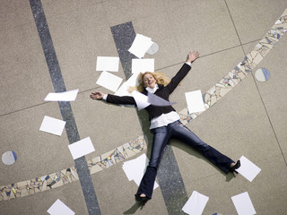 Frau auf dem Boden liegend von Papieren umgeben, erhöhte Ansicht