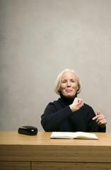 Seniorin sitzt am Tisch mit Buch, lächelnd