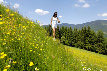 Junge Frau zu Fuß mit Skistock auf Wiese