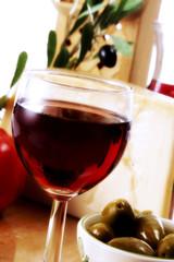 Ein Glas Rotwein und grünen Oliven