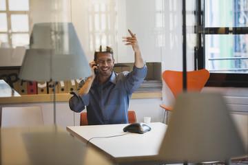 Junger Mann im Büro mit Telefon