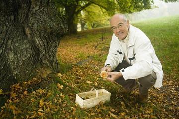 Deutschland, Baden-Württemberg, Schwäbische Alb, älterer Mann beim Pilze sammeln